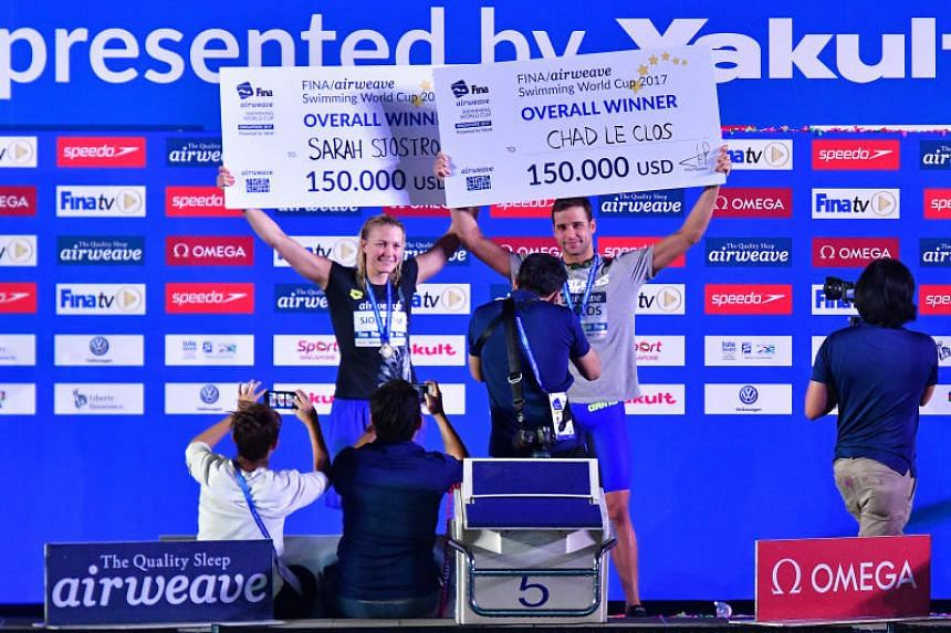 South Africa's Chad le Clos and Swede Sarah Sjostrom celebrating with their winning Fina Swimming World Cup pay cheques.