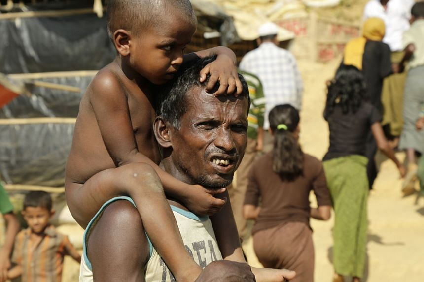 A Rohingya refugee stands with his son at the Kutupalong camp, Coxabazar in Bangladesh on Nov 19, 2017.