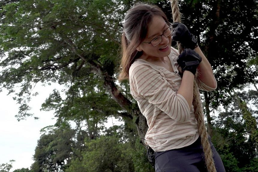 Straits Times journalist Ng Huiwen pulling herself up a rope, scaling a 1.5m-high wall (below), and going through a scenario-based drill - a simulated gunman attack (right) - with officers from the police's elite Emergency Response Team moving in to