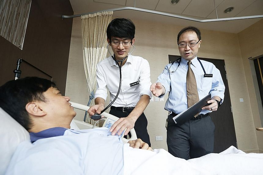 Dr Jonathan Yap (left), associate consultant in the National Heart Centre Singapore's cardiology department, seeing a patient with his mentor, Associate Professor Yeo Khung Keong, a senior consultant. The mentorship programme is among hospital scheme