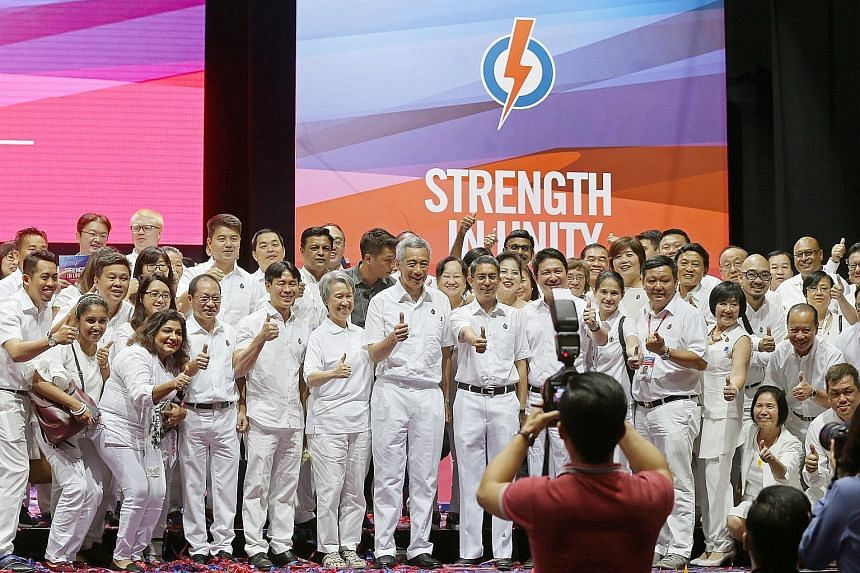 Left: Prime Minister Lee Hsien Loong and Mrs Lee taking a photo with party members yesterday. In his speech, PM Lee recapped the Government's work since it began its term in January last year, and outlined the work to come. Below: PAP members taking