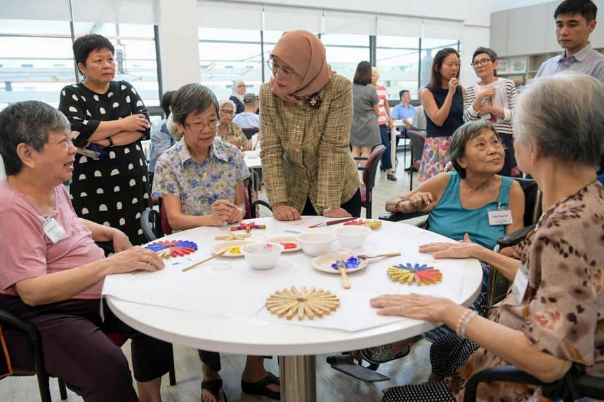 President Halimah Yacob joins senior citizens in painting trivets made from clothes pegs at the Community for Successful Ageing Whampoa Centre on Monday (Nov 20).