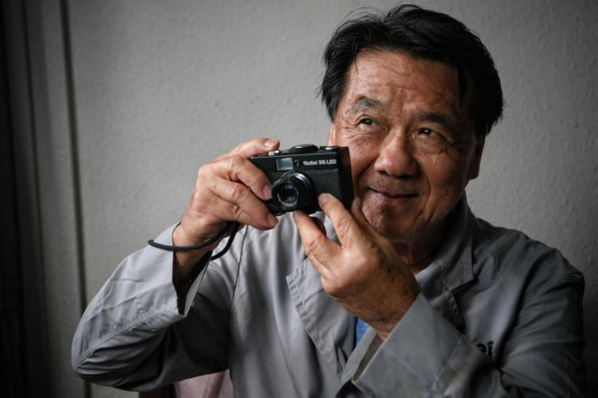 Mr Chong Nam Soy wearing his old Rollei uniform and holding a Rollei 35 compact camera which he assembled in the past.