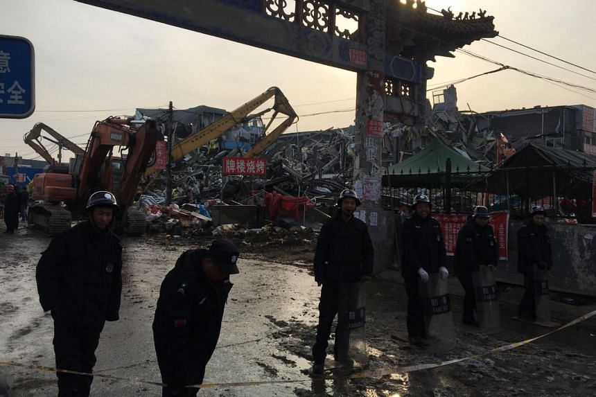 Police stand guard as demolition works take place at the site of the fatal housing block fire in Beijing.