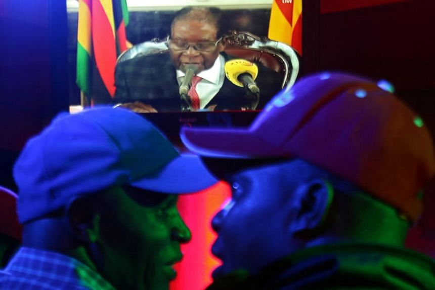 Zimbabweans watch as Robert Mugabe addresses the nation on television, at a bar in Harare on Nov 19, 2017.