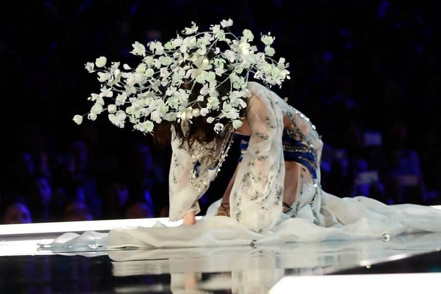 Chinese model Ming Xi falls on the catwalk.