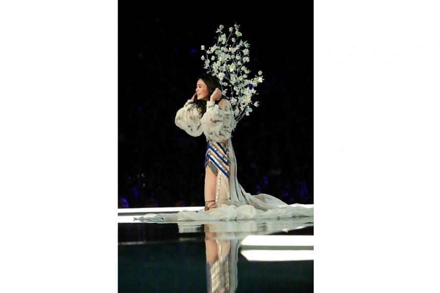 Chinese model Ming Xi laughs after falling on the catwalk.