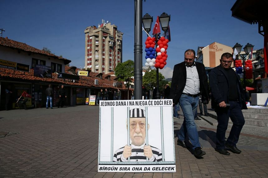"""A banner depicting US-based Turkish cleric Fethullah Gulen on a street in in Novi Pazar, Serbia on Oct 11, 2017. The banner reads, """"His turn will come one day""""."""