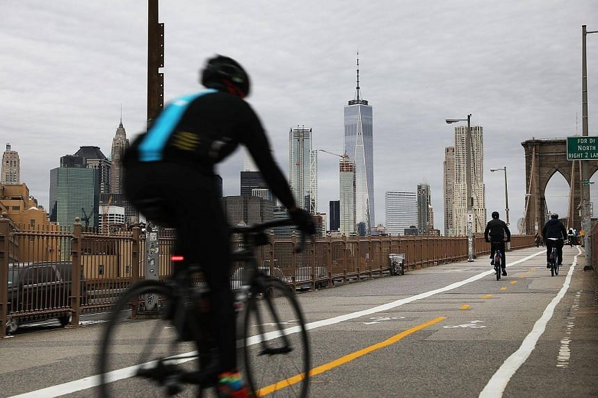 People ride bikes across the Brooklyn Bridge in New York City.