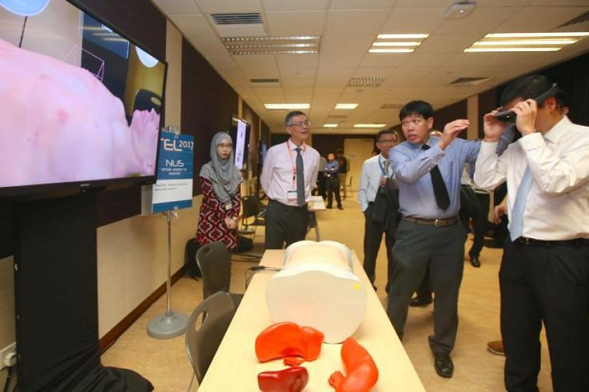 Minister Ong Ye Kung (right) wearing a HoloLens as Associate Professor Erle Lim (centre, in blue) demonstrates the MediSIM, an augmented reality surgery training tool.