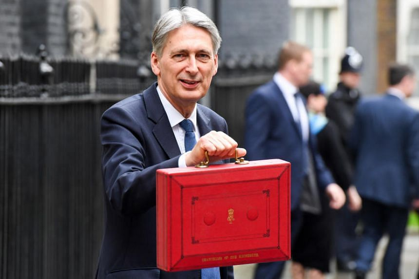 British Finance Minister Phillip Hammond with a red official box as he exits 11 Downing Street on his way to present his first annual budget statement in the House of Commons in London, UK on March 8, 2017.