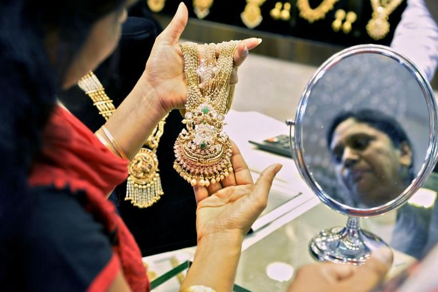 An Indian customer looks at gold jewellery at a stall in the Asia Jewels Fair 2017 held in Bangalore.
