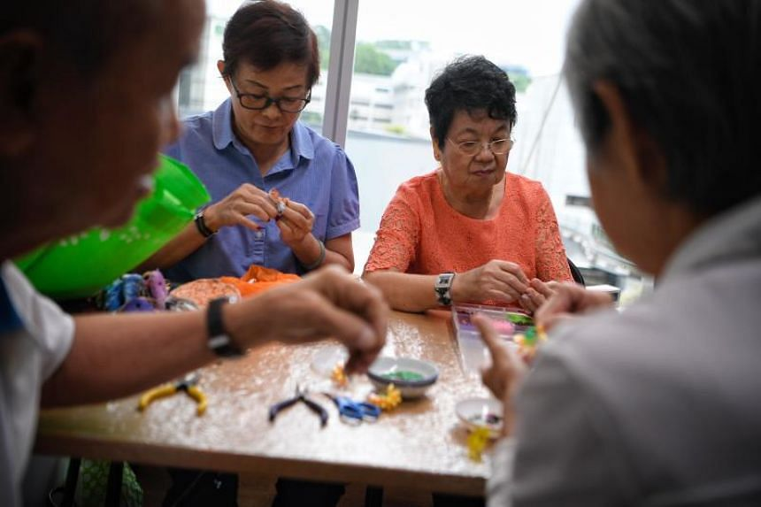 Ms Tan Kim Eng (right), 75, and Ms Betty Tan, 67, volunteers with the Caregiving Welfare Association, making local crafts at the new Caregivers Sanctuary in the National University Hospital on Nov 21, 2017.