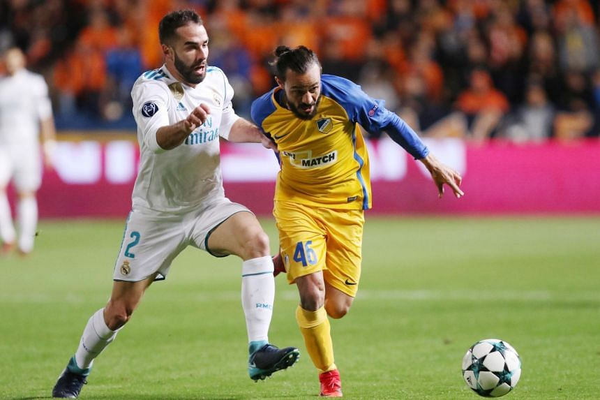 Real's Dani Carvajal (left) vies for the ball against Stathis Aloneftis of Apoel FC.