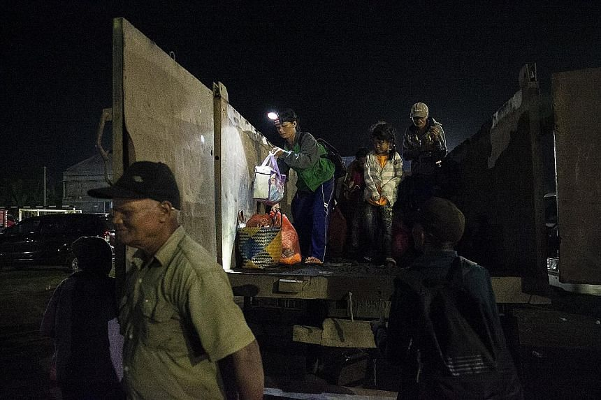 Evacuees arriving at an emergency shelter in Klungkung, Bali, yesterday. Mount Agung began erupting yesterday and it is reported that the height of the smoke has exceeded 700m from the peak of the mountain.