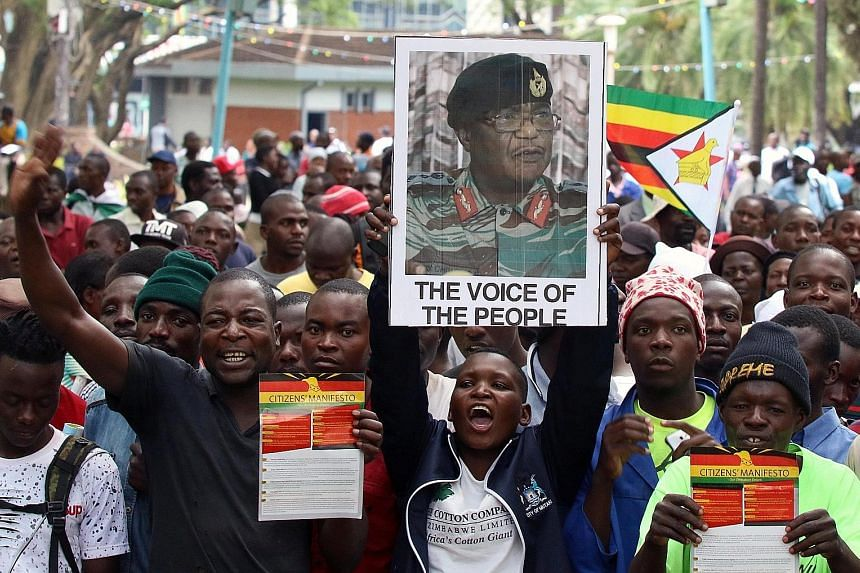 Protesters against Mr Robert Mugabe outside Parliament in Harare yesterday. Wild celebrations broke out at a joint sitting of Parliament when Speaker Jacob Mudenda announced Mr Mugabe's resignation and suspended the impeachment procedure. Protesters