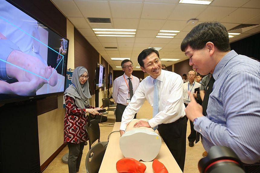 Minister Ong Ye Kung (centre) examining an interactive abdominal manikin yesterday as NUS Associate Professor Erie Lim (right) demonstrates how MediSIM, an augmented reality surgery training program, works.