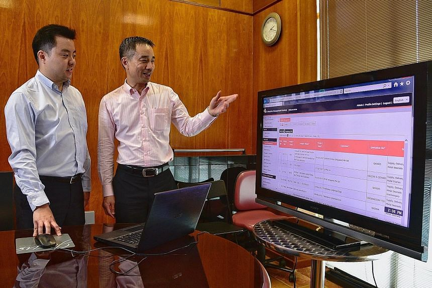 Tacam Steel general manager Brian Wong (left) and Enhanzcom CEO Edwin Seah with the Enhanzcom's Web-based software. Adopting the system customised to Tacam Steel's needs has shaved off about $4,500 in manpower costs each month, and reduced paperwork