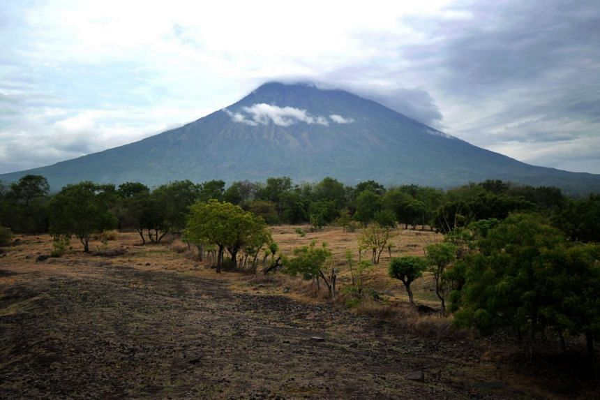 Mount Agung belched smoke as high as 700 metres above its summit late Tuesday afternoon (Nov 21), sparking an exodus from the settlements near the mountain.
