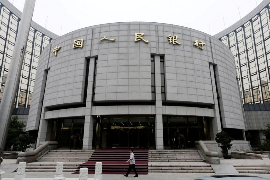A staff member walks in front of the headquarters of the People's Bank of China, the central bank, in Beijing.