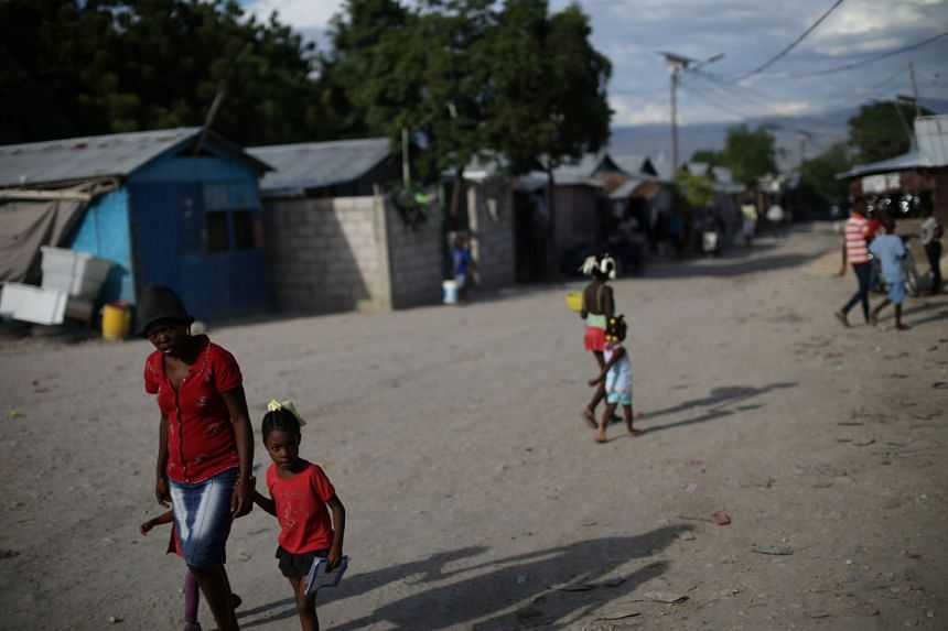 People walk in a camp for people displaced by the Jan 2010 earthquake in Port-au-Prince, Haiti.