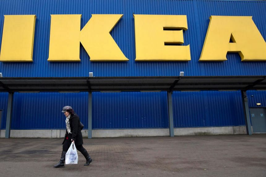 A shopper walks past a sign outside an IKEA store in Wembley, north London.