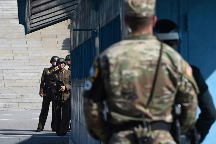 North Korean soldiers (left) look at the South side at the truce village of Panmunjom in the Demilitarized Zone (DMZ) on the border between North and South Korea. PHOTO: AFP
