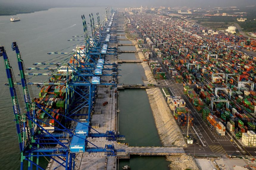 Container ships sit docked next to gantry cranes at Port Klang.