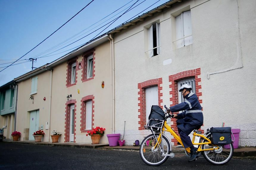A postman of French postal service company La Poste distributes letters using an electrically-assisted bicycle in Vertou, France.
