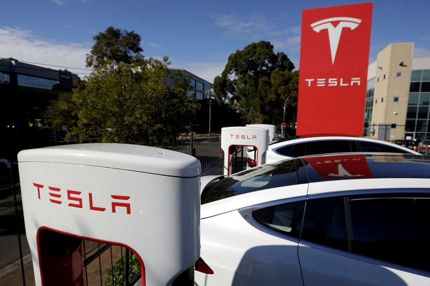 Tesla Model X cars are charged by superchargers at an electric car dealership in Sydney.