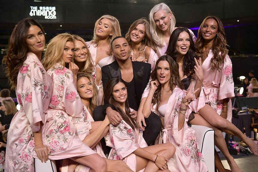 Victoria's Secret Fashion Show models posing with Olivier Rousteing, creative director of Balmain.