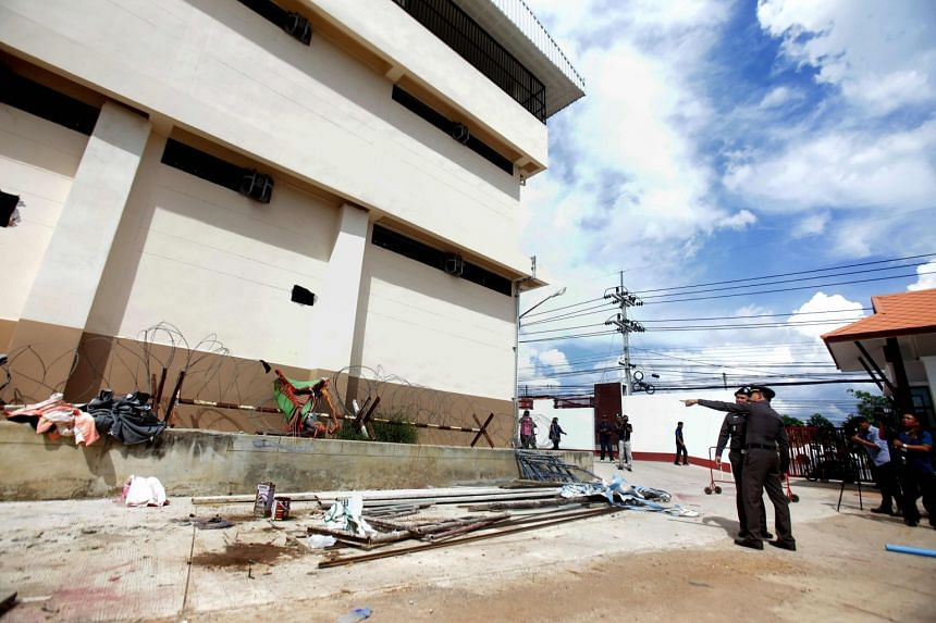 Police point at holes through which 20 ethnic Uighurs escaped from an immigration detention centre in Sadao district in the southern Thai province of Songkhla.