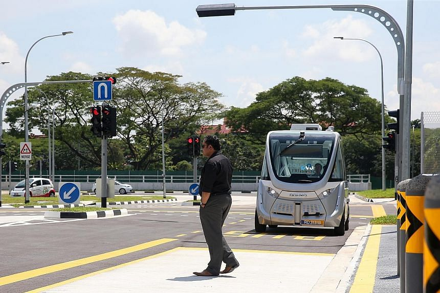 """A """"jay-walker"""" passing in front of a Navya self-driving shuttle bus at the new autonomous vehicle test centre. It will provide a """"safe, controlled and configurable"""" testing environment for AV developers to test their technologies using a range of sim"""