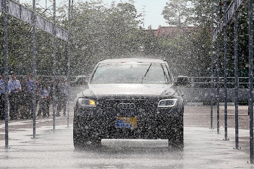 A Delphi self-driving car going through a rain simulator. The centre also has a flood zone to test the navigation abilities of autonomous vehicles in adverse weather.