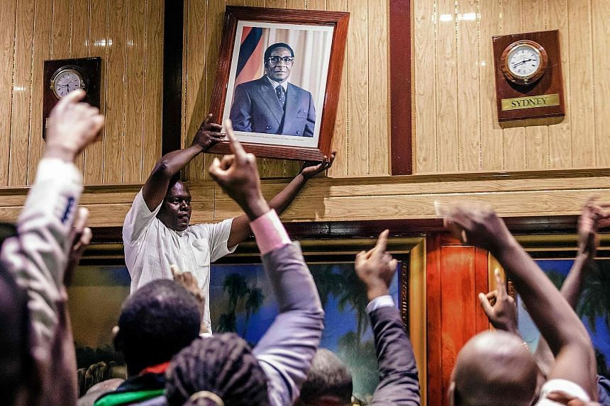 A portrait of Mr Robert Mugabe being removed from the wall at the Rainbow Towers conference centre in Harare, after his resignation on Tuesday. The portrait was torn apart and stomped to pieces by the cheering crowd, as Mr Mugabe's nearly four-decade