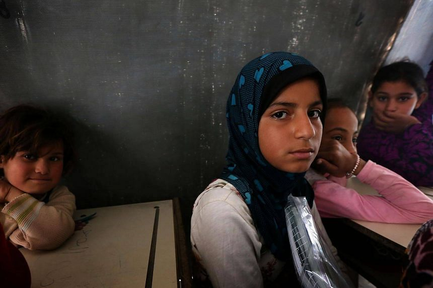 Displaced Iraqi children from the the city of Mosul attend class at a United Nations Children's Fund school at the Hasan Sham camp, east of Arbil in Iraq.