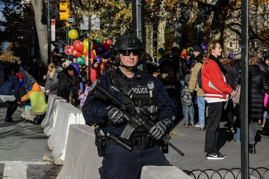 A member of the New York City police department stands guard while Macy's inflation teams inflate balloons near Central Park ahead of the Macy's Thanksgiving Day parade on in New York City.