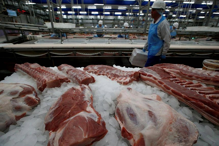 An employee walks past sorted pieces of meat at a pork processing plant,  in the village of Borschevka, in Tambov region, Russia.