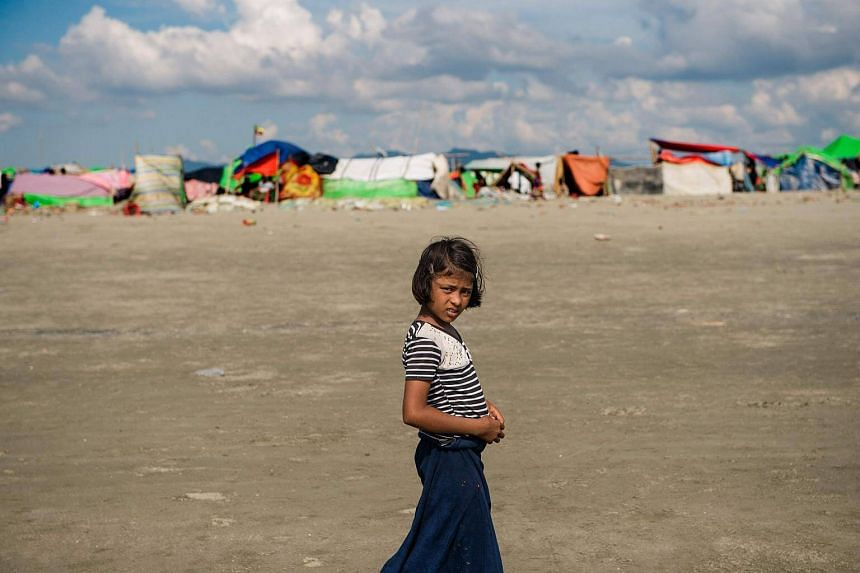A girl stands on the sandy banks of the natural boundary between Myanmar and Bangladesh near a makeshift camp in Rakhine state in Myanmar.