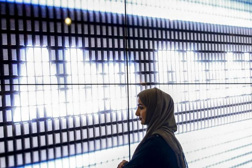 A woman pictured against the a display reading Abu Dhabi at a booth during the Fintech Festival in Singapore on Nov 15, 2017. Singapore and Abu Dhabi have a long-standing cooperation in the securities field through, for example, a FinTech Innovation