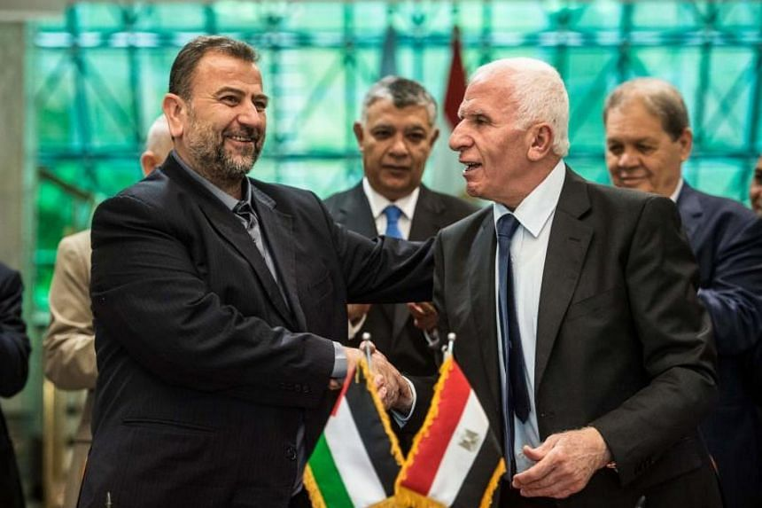 Fatah's Azam al-Ahmad (right) and Saleh al-Aruri (left) of Hamas shake hands after signing a reconciliation deal in Cairo on Oct 12, 2017, as the two rival Palestinian movements ended their decade-long split following negotiations overseen by Egypt.