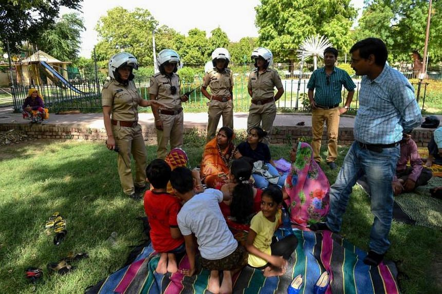 Members of a newly launched female patrol unit explains to women and children about the women's helpline numbers in a park in Jaipur, India on June 14, 2017.
