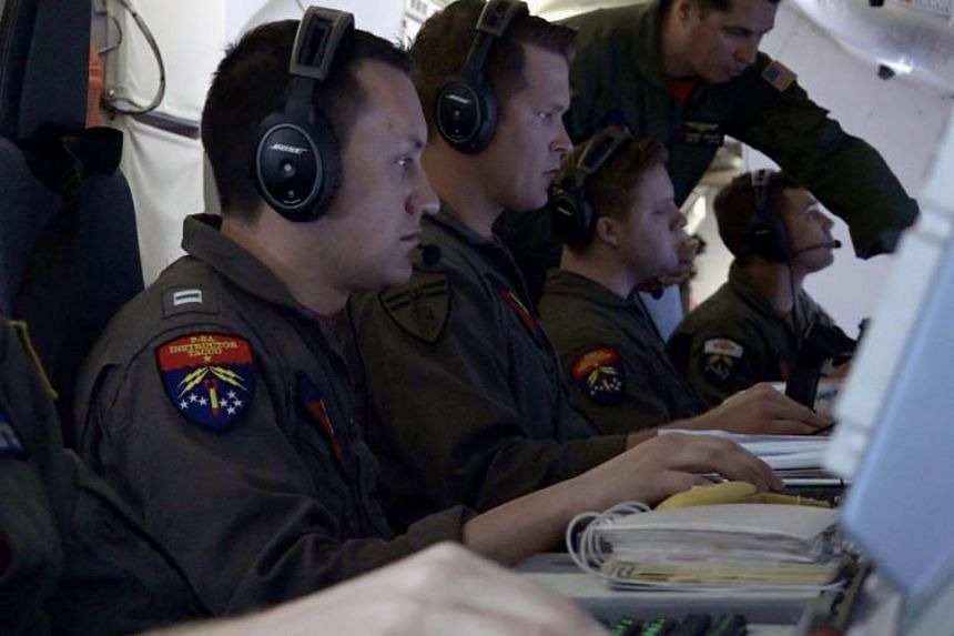 US Navy flight officer Zachary Collver, mission commander at the Boeing P-8A Poseidon aircraft, works alongside other officers during the search for the ARA San Juan submarine missing at sea as they fly over the South Atlantic Ocean, Argentina on Nov