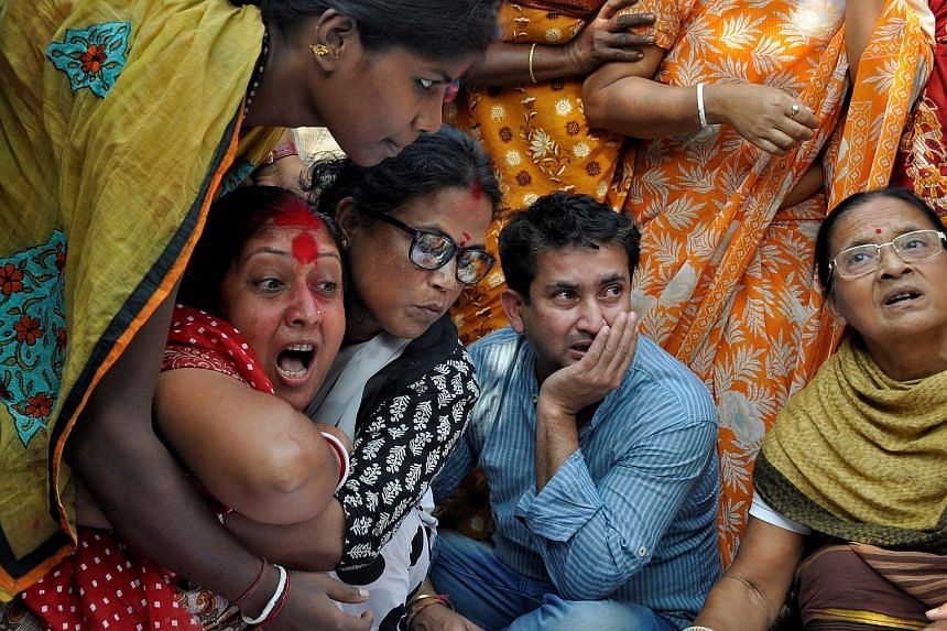 The wife (in red) of slain journalist Sudip Dutta Bhaumik mourning next to her husband's body, on Nov 22, 2017.