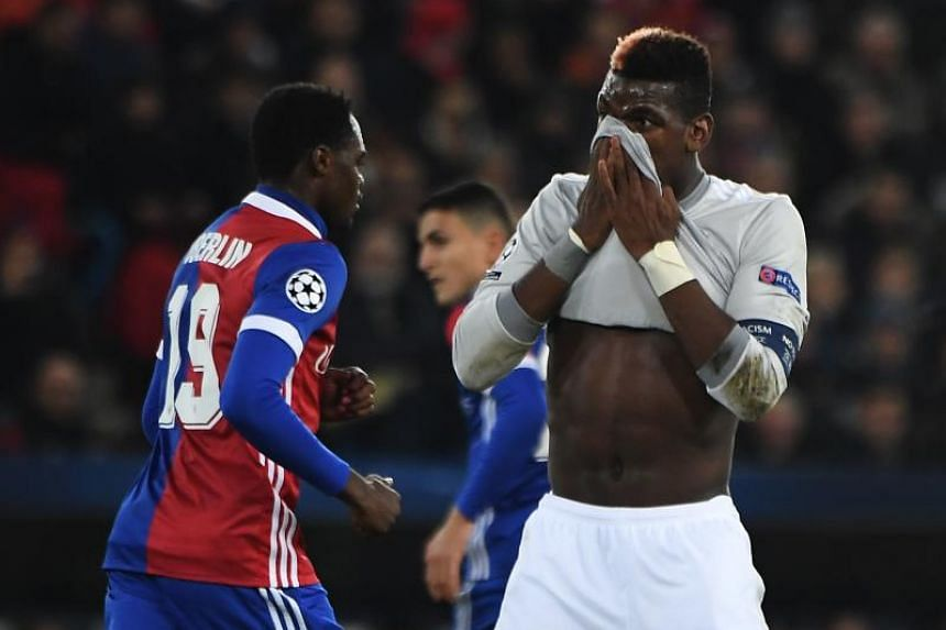 Manchester United's Paul Pogba (right) reacts as Basel's Dimitri Oberlin walks past during their Uefa Champions League group match.