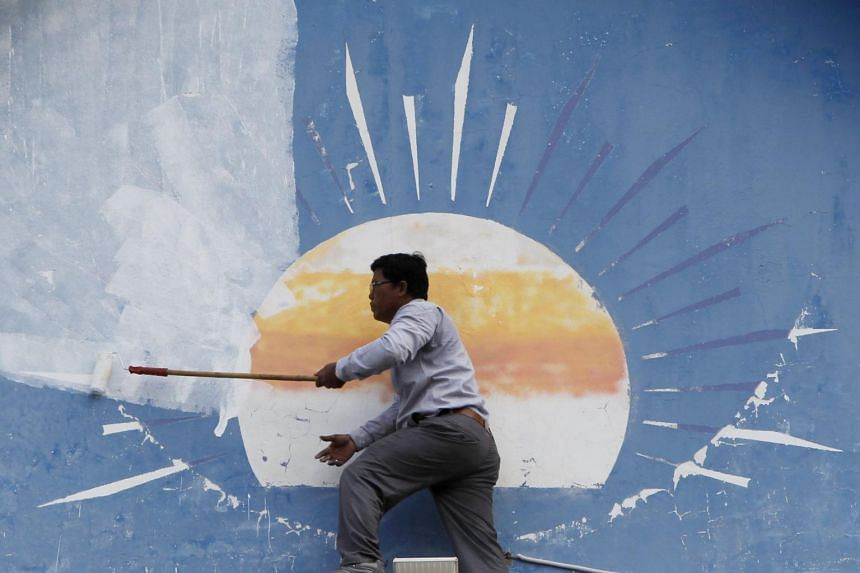 A Cambodian worker paints over the opposition Cambodia National Rescue Party's logo at its headquarters in Phnom Penh, Cambodia.