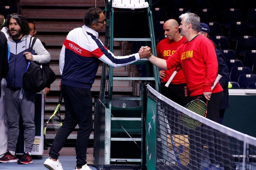 Belgian captain Johan van Herck Shakes hands with his French counterpart Yannick Noah during training on Nov 23, 2017.