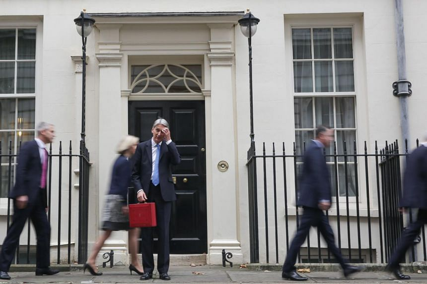 British Chancellor of the Exchequer Philip Hammond (centre) leaving his official residence with the Budget Box before presenting the government's annual budget to Parliament on Nov 22, 2017.