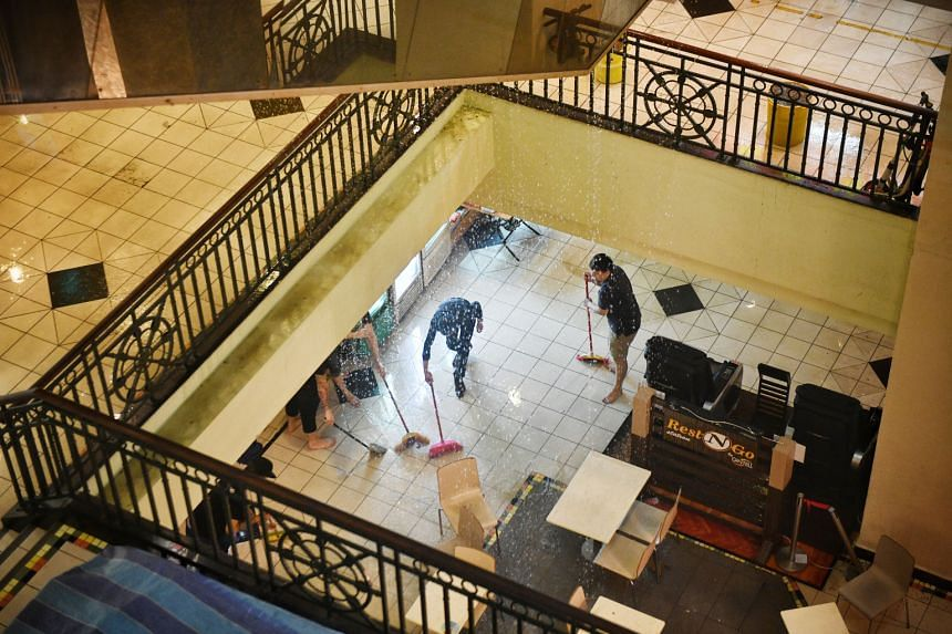 People sweeping water away from shops in the basement of Parklane Shopping Mall in Selegie Road, after a fire was extinguished by sprinklers yesterday evening. No injuries were reported, said the Singapore Civil Defence Force, which responded to the