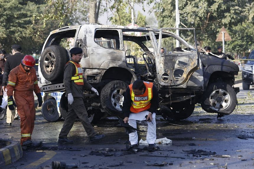 Pakistani security officials inspect the scene of a bomb attack that targeted a senior police officer in Peshawar on Nov 24, 2017.
